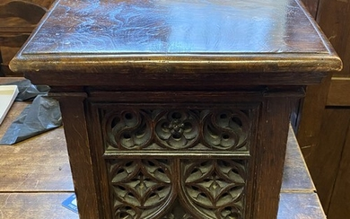 A stool, the elm top on an oak base with gothic carved decor...