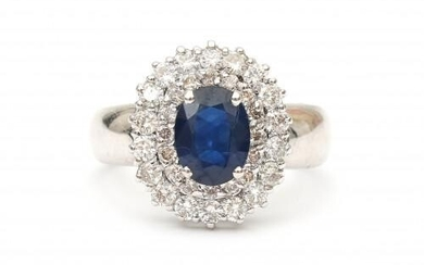 An 18 carat white gold diamond and sapphire cluster ring. Set with an oval faceted cut sapphire surrounded by thirty four brilliant cut diamonds, ca. 0.52 ct. in total, ca. F-G, VS2. Gross weight: 4.7 g.