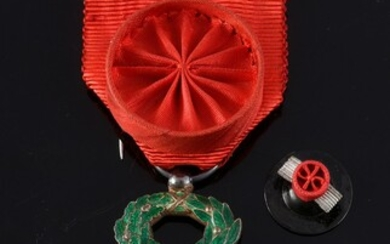 ORDER OF THE LEGION OF HONOUR (France). Knight's cross, silver, gold and enamel, with rosette ribbon in red moiré silk taffeta. A collar lapel rosette is attached. Accidents. H.: 5.5 cm - W.: 3 cm.See illustration on page 24.