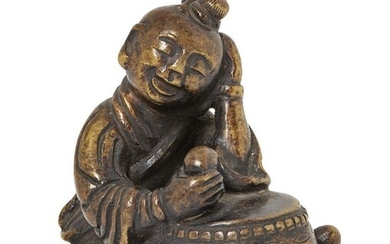 Property of a Gentleman (lots 36-85) A Chinese bronze scroll weight, Ming dynasty, 17th century modelled as a seated boy playing a large drum, 5cm high