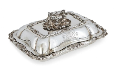 A George IV silver entrée dish and cover, London, c.1829, William Ker Reid, of rectangular form, with applied shell and foliate scroll rim, the cover with foliate twist handle and engraved armorial to two sides, the motto reading 'non sine...