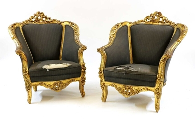 A pair of gilt armchairs