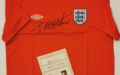 A 1966 England replica jersey t-shirt signed by Sir Geoff Hurst (British, b. 1941) with certificate.