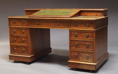 An Edwardian mahogany pedestal desk, the top inset with green leatherette, having hinged writing slope enclosing storage space and flanked by two drawers, over an arrangement of eight drawers, raised on castors, 87cm high, 151cm wide, 77cm deep