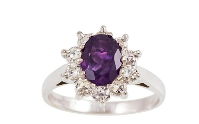 A DIAMOND AND AMETHYST CLUSTER RING, the oval amethyst to a ...