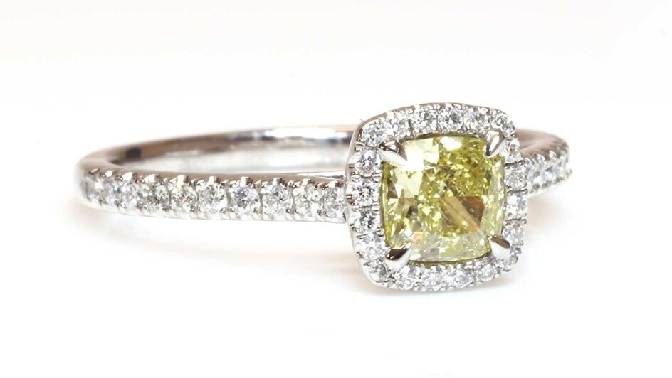 A platinum fancy yellow diamond and diamond halo cluster ring