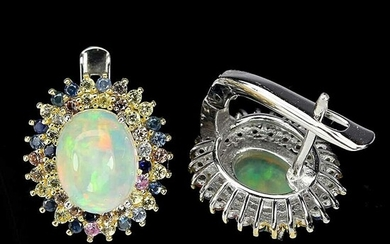 A pair of opal and sapphire ear studs each set with a a cabochon opal...