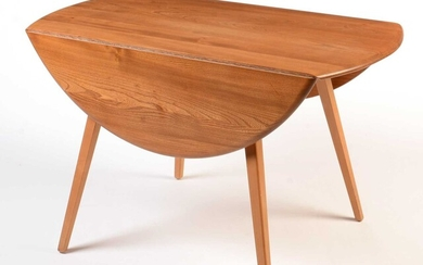 Ercol: a light beech and elm round-shaped drop-leaf dining table.