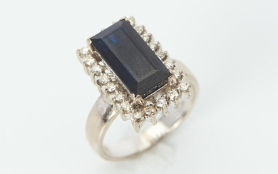 A SAPPHIRE AND DIAMOND RING IN 18CT WHITE GOLD, FEATURING A RECTANGULAR CUT SAPPHIRE OF 4.697CTS, WITHIN A SURROUND OF TWENTY TWO RO...
