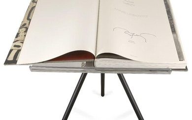 Annie Leibovitz, American b.1949 Annie Leibovitz SUMO, 2014; hardcover book with eight fold outs, signed in black marker and numbered 5712/10,000 to the title page, 467 pages; together with a tripod book stand designed by Marc Newson, published by...
