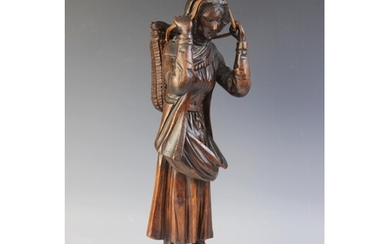 A Northern European folk art carved figure of a fisher woman...
