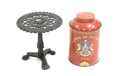A black painted cast iron trivet in the form of a tripod table