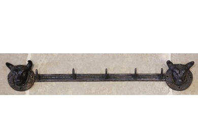 A cast iron wall mounted coat or hat rack, the five hook rai...
