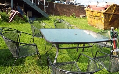 A garden table and a set of six metal hoop back mesh seated ...