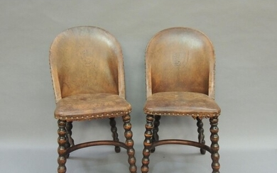A pair of tan leather and close nailed single chairs, the tu...