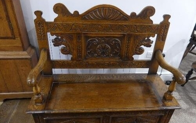 An early 20thC box seat Oak Settle, the two panel front with...
