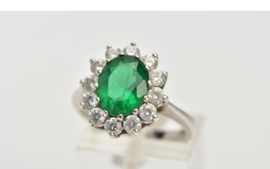 A 9CT WHITE GOLD CLUSTER RING, centring on an oval cut green...