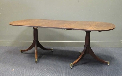 A George III style mahogany twin pedestal dining table with one leaf, early 20th century, the