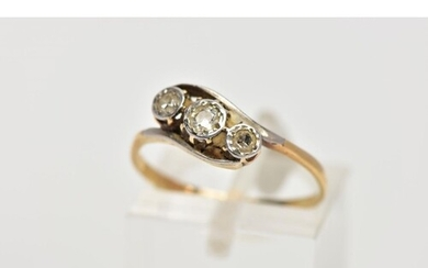 A YELLOW METAL, THREE STONE DIAMOND RING, of a crossover des...