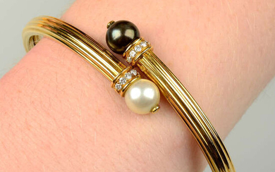 An 18ct gold grooved crossover bangle, with vari-hue cultured pearl and brilliant-cut diamond terminals, by Boodles.