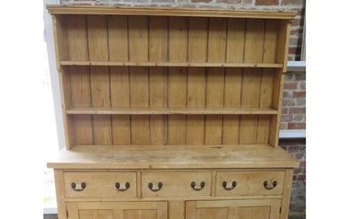A 19th century stripped pine dresser with an open rack top a...