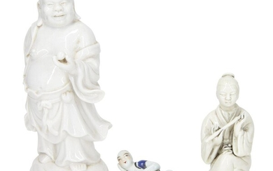 A Chinese Dehua porcelain figure of Han Xiangzi, late 19th/early 20th century, modelled seated with crossed legs holding a flute in both hands, impressed Dehua and He Chaozong seal marks to the back, 11.4cm high, together with a Dehua porcelain...