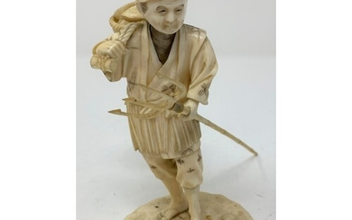 A Japanese carved ivory figure, of a shell fisherman, carryi...