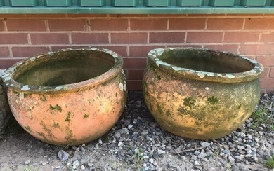A large pair of circular terracotta planters.