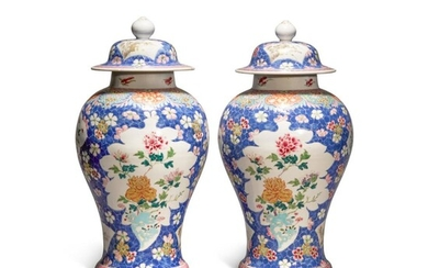 A pair of blue-ground famille-rose 'floral' baluster jars and covers, Qing dynasty, Qianlong period   清乾隆 藍地粉彩開光花卉紋蓋罐一對