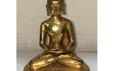 A Chinese bronze gilded figure of a buddha in lotus position...