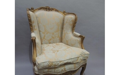 A French gilt armchair having an encircling moulded and flor...