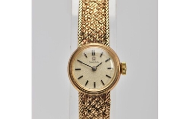 A 9CT GOLD LADY'S OMEGA WRISTWATCH, the circular face with b...