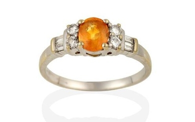 A Yellow/Orange Sapphire and Diamond Ring, the oval cut yellow...