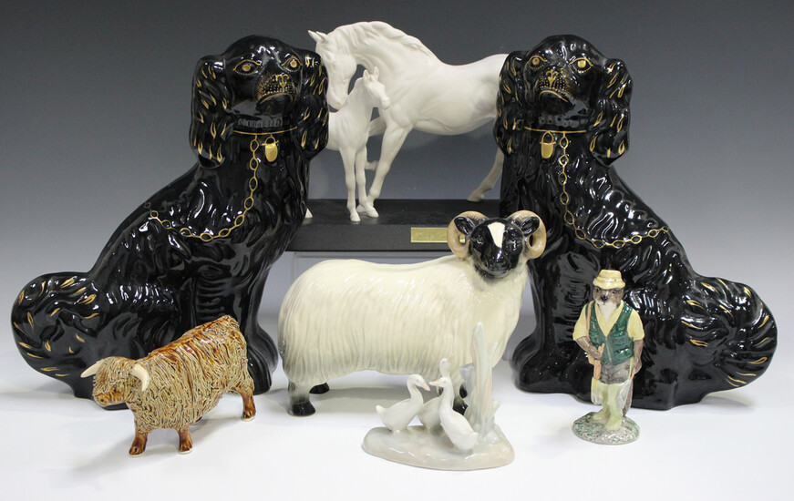 A pair of Jackfield type black glazed Staffordshire spaniels, late 19th century, with gilt detail, h