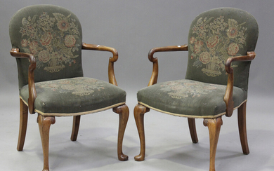 A pair of early 20th century walnut framed shepherd's crook elbow chairs, each upholstered in n