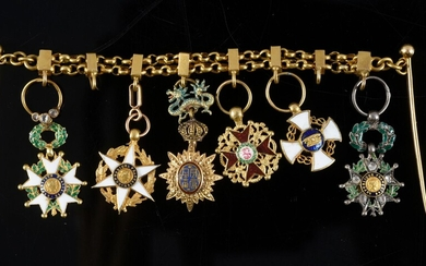 BAR FOR MINIATURE DECORATIONS. Two gold chains hold the miniature orders of the Legion of Honour with diamond roses, the Agricultural Merit, the Dragon of Annam, Saint-Stanislas, the Crown of Italy and the Legion of Honour set with diamond roses...