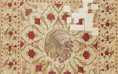 A Mughal embroidered floor spread, India, 18th century, for the European market, the cotton ground quilted and embroidered in silk and metal thread with a border of flowers, the field with a central, Chinese-style phoenix, 144 x 158cms. Provenance:...