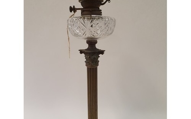 A brass oil lamp, with a cut glass well, base in form of a c...