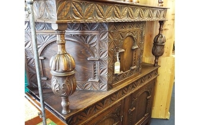 A carved oak court cabinet having central cabinet above a do...
