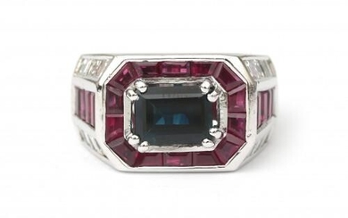 An 18 karat white gold sapphire, ruby and diamond ring. A Of geometrical design featuring a rectangular cut blue sapphire of ca. 2 ct. surrounded by carré cut rubies. The shoulders are set with eight carré cut rubies and sixteen carré cut diamonds, ca...