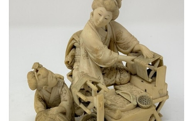 A Japanese carved ivory group, of a lady spinning, with an a...