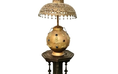 A Tibetan gilt metal lamp base of rounded form, applied with...