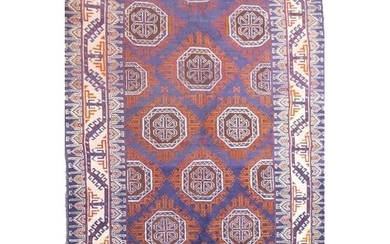 A blue ground Middle Eastern wool rug with a Bokhara style d...