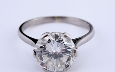 A large and impressive diamond solitaire ring, on white meta...