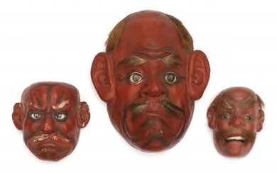 A set of three red lacquer Japanese Noh masks with glass eyes and facial hair. Meiji period (1886-1912).