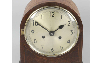 An early 20th century inlaid mahogany cased arch topped mantel clock.