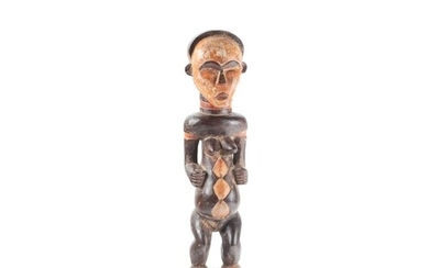 A Punu standing female figure, Gabon, the face painted in a ...