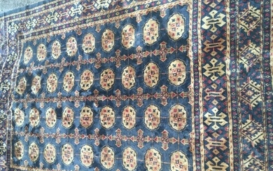 A hand knotted rug with a geometric gold pattern on a blue g...