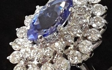 An 18ct white gold cluster ring set with a marquise cut tanzanite surrounded by brilliant cut diamonds, (U).