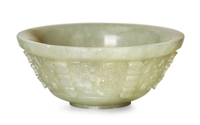 Property of a Gentleman (lots 36-85) A small Chinese green jade archaistic bowl, 18th century, finely carved with taotie masks interspersed with six rows of three ingot-shaped flanges, 8cm diameter, later hardwood stand